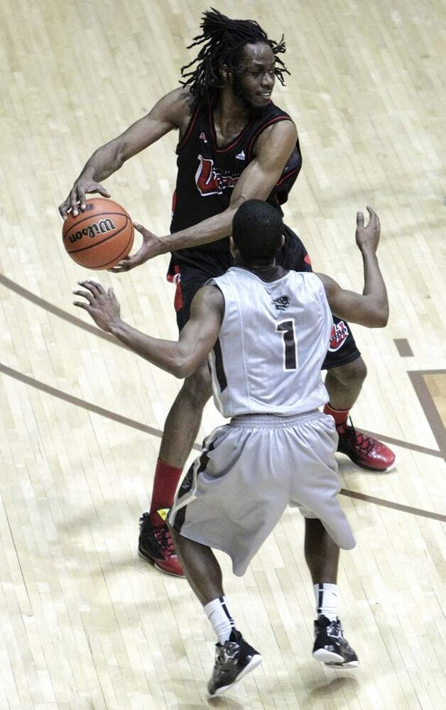 The University of Winnipeg Wesmen played the University of Manitoba Bisons men's basketball team for a spot in the playoffs at the Investors Group Athletic Centre Wednesday evening. The Wesmen won 89-85.  Wesmens' Benny Iko (11) looks for an opening while Bisons' Stephan Walton (1) tries to block a pass in the first half of the game.   (Mike Deal / Winnipeg Free Press)