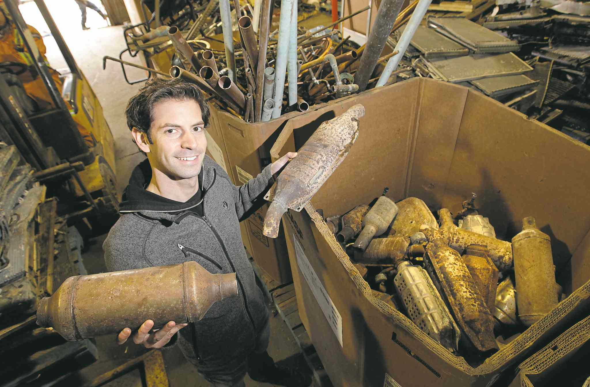 Adam Chisick of Urbanmine Metal Recycling holds two catalytic converters that could be worth between $5 to several hundred dollars.