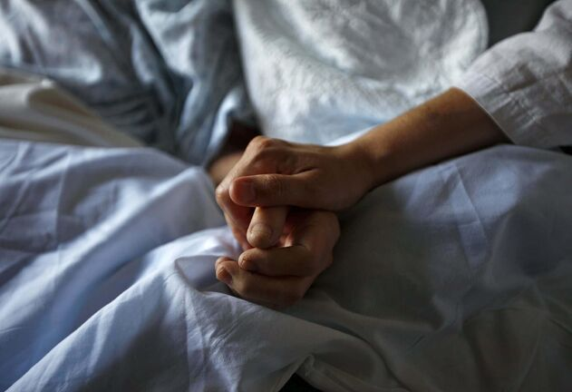 A woman holds the hand of her mother who is dying from cancer during her final hours at a palliative care hospital in Winnipeg.