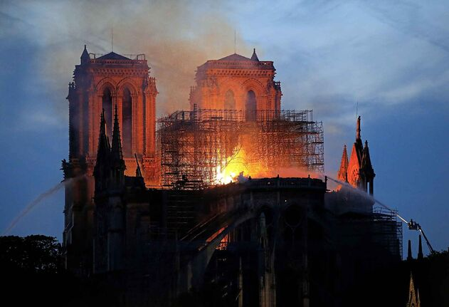 Firefighters tackle the blaze as flames and smoke rise from Notre Dame cathedral as it burns.  (Michel Euler / The Associated Press)