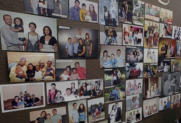 Winkler, Manitoba-Adele Dyck of Star 7 International, immigration brokerage firm that started the Provincial  Nominee Program in MB. Stands by wall of photos of potential immigrants-See Bill Redekop  story- Jan 14, 2014   (JOE BRYKSA / WINNIPEG FREE PRESS)