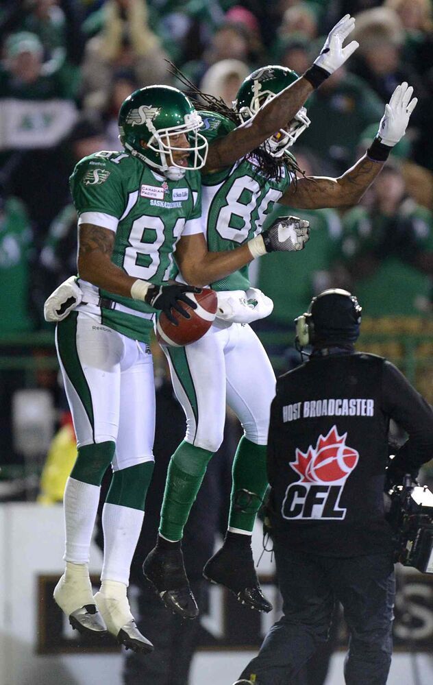 Saskatchewan Roughriders slotback Geroy Simon (left) celebrates his second touchdown against the Hamilton Tiger-Cats with teammate wide receiver Taj Smith during the second quarter. (Jonathan Hayward / The Canadian Press)