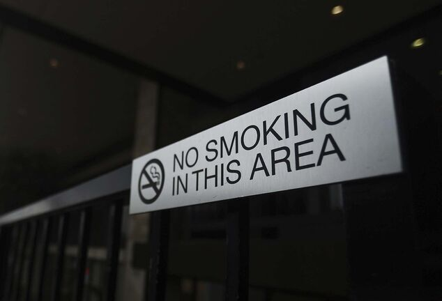 A 'No Smoking' sign is seen outside of a business on Wilshire Boulevard on May 10, 2019 in Beverly Hills, Calif. Beverly Hills will likely become the first city in the country to ban most sales of tobacco. If a proposed measure passes in the City Council later this month, sales of tobacco products would be banned in gas stations, pharmacies, and grocery stores. Only the city's three recognized cigar lounges would be allowed to continue to sell tobacco products. (Mario Tama/Getty Images/TNS)</p>