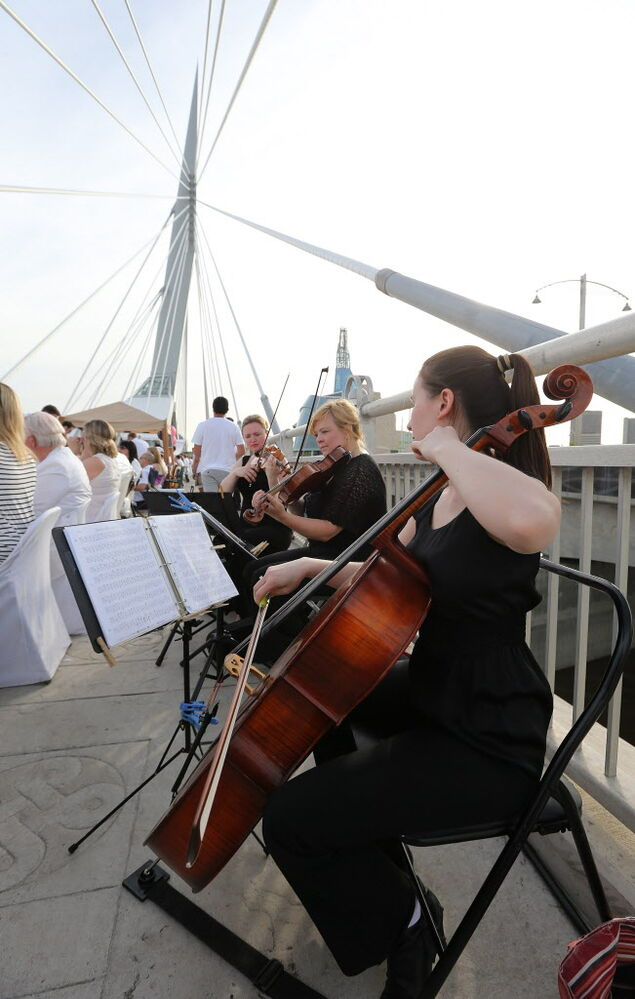 A string trio plays for diners as they enjoy their food and their view.