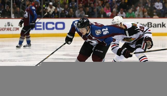 Colorado Avalanche left wing Gabriel Landeskog, left, of Sweden, reaches for puck as Chicago Blackhawks center Jonathan Toews defends during the third period of the Blackhawks' 3-2 victory in an NHL hockey game in Denver on Wednesday, Nov. 26, 2014. (AP Photo/David Zalubowski)
