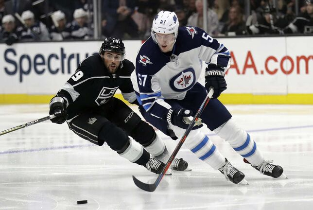 Tyler Myers, right, controls the puck in front of Los Angeles Kings' Alex Iafallo during the second period. (Marcio Jose Sanchez / The Associated Press)