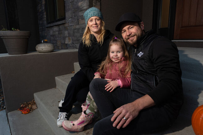 Dawn and Mike McEwen outside their home with their daughter Vienna. (Jesse Boily / Winnipeg Free Press)