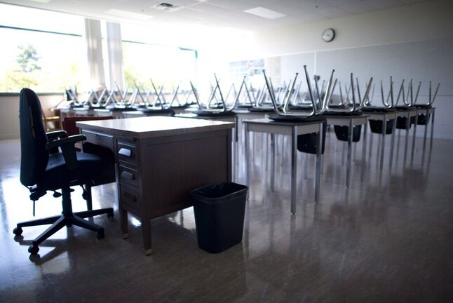 An empty teacher's desk is seen at the front of a empty classroom at McGee Secondary school in Vancouver on September 5, 2014. THE CANADIAN PRESS/Jonathan Hayward