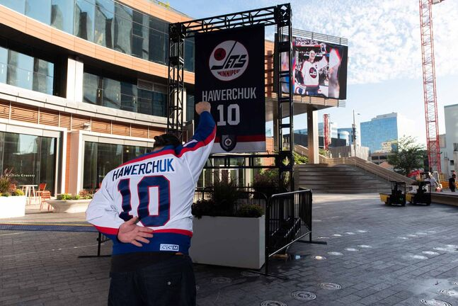 Winnipeg Jets and Dale Hawerchuk fan Marco Almeida shows his respect at the Dale Hawerchuk banner in True North Square on Tuesday.
