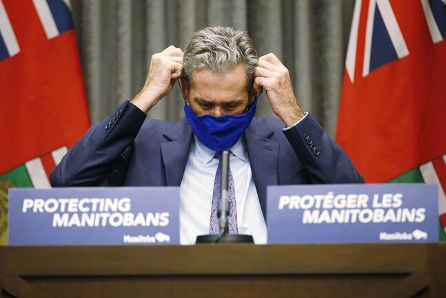 JOHN WOODS / WINNIPEG FREE PRESS  Premier Brian Pallister puts on his mask after speaking to media during a COVID-19 press conference at the Manitoba Legislature in Winnipeg Monday, November 16, 2020. Pallister announced funding for small businesses.    Reporter: ?
