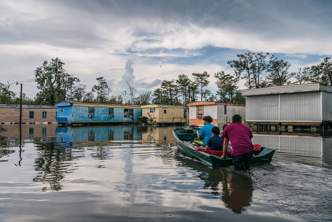 The Maldonado family travel by boat to their home after it flooded during Hurricane Ida, on Tuesday in Barataria, La. (Brandon Bell / Getty Images/TNS)