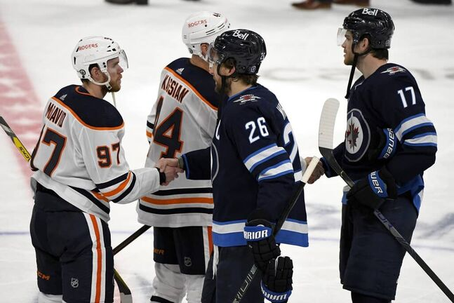 Winnipeg Jets' Blake Wheeler (26) shakes hands with Edmonton Oilers' Connor McDavid (97) after the Jets eliminated the Oilers following third overtime period NHL Stanley Cup playoff action in Winnipeg on Tuesday, May 25, 2021. THE CANADIAN PRESS/Fred Greenslade
