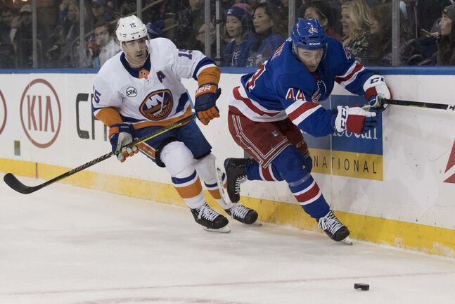 In January, New York Rangers defenseman Neal Pionk (44) and New York Islanders right wing Cal Clutterbuck (15) chase the puck during the first period of an NHL hockey game in New York.