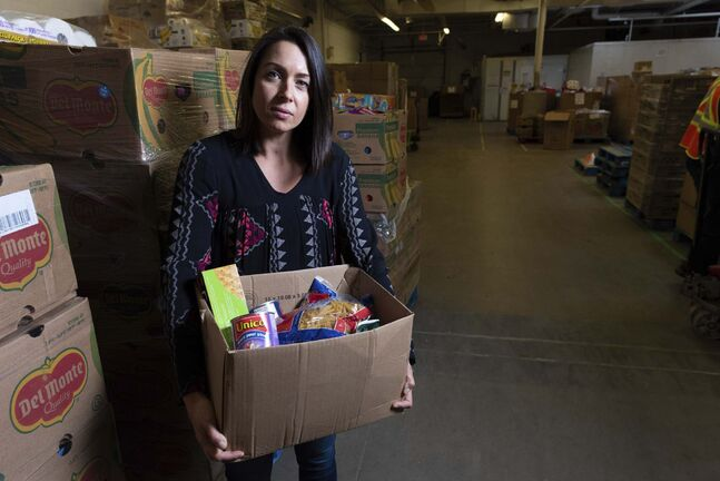 JESSE BOILY / WINNIPEG FREE PRESS</p><p>Meaghan Erbus, advocacy and impact manager at Winnipeg Harvest, shows a hamper at the Winnipeg Harvest warehouse.</p>