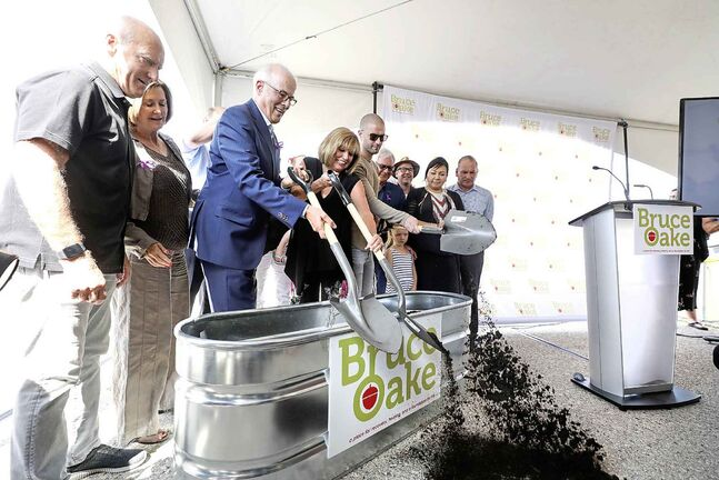 With many supporters by their side the Oake family, Scott, Anne and their son Darcy, shovel a scoop of dirt on the ground in the parking lot of what is to become the Bruce Oake Recovery Centre during a ceremonial groundbreaking and capital campaign launch on Thursday afternoon.