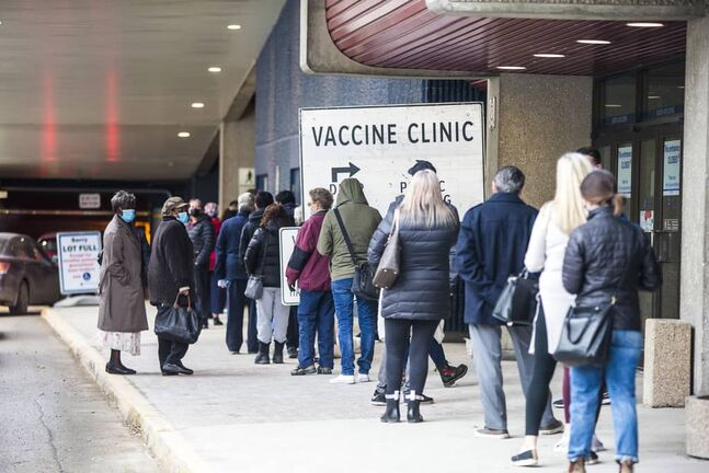 MIKAELA MACKENZIE / WINNIPEG FREE PRESS    A lineup for the vaccine supercentre stretches from the RBC Convention Centre entrance on York Avenue around the building on Carlton Street in Winnipeg on Thursday, March 25, 2021.      Winnipeg Free Press 2021