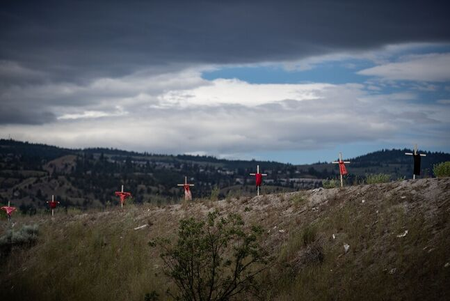 Children's dresses are hung on a crosses near the former Kamloops Indian Residential School, to honour the 215 children whose remains have been discovered buried near the facility, in Kamloops, B.C. (Darryl Dyck / The Canadian Press files)