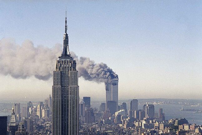 In this Sept. 11, 2001 file photo the twin towers of the World Trade Center burn behind the Empire State Building in New York after terrorists crashed two planes into the towers causing both to collapse.(AP Photo/Marty Lederhandler)