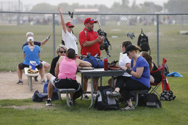 Players ignore social distancing guidelines as they gather around a picnic table prior to their game at Little Mountain Sportsplex Thursday.