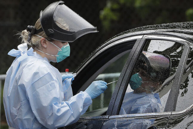 A medical worker administer a test for the coronavirus to a person in a vehicle, Thursday, June 11, 2020, in the Roxbury neighborhood of Boston. Boston is offering those who were involved in protests following the killing of George Floyd access to coronavirus testing at the mobile site whether or not they are showing signs of COVID-19. Floyd, who was black, died May 25th after a white Minneapolis police officer pressed a knee on his neck as he pleaded for air. (AP Photo/Steven Senne)