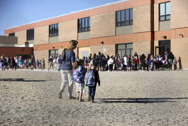 Teachers at Park Elementary School in Casper, Wyo., lead students by grade in to the school while following new health guidelines, Wednesday, Sept. 2, 2020. (Cayla Nimmo/The Casper Star-Tribune via AP)