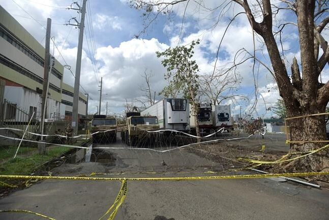 FILE - In this Oct. 2, 2017 file photo, three containers for holding corpses, right, sit parked outside the Institute of Forensic Science, brought to give support in the aftermath of Hurricane Maria in San Juan, Puerto Rico, where the institute press spokesman confirmed their facilities no longer provided enough space to store bodies, and that several hospital morgues are also full. Along with post-storm conditions, each death has a complex mix of causes that can include serious pre-existing conditions and individual decisions by patients, caregivers and doctors, making it difficult to definitively apportion blame in every case. But critics say many could have been saved by better preparation and emergency response. (AP Photo/Carlos Giusti, File)