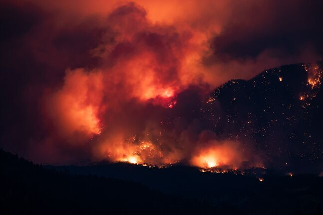 A wildfire burns on the side of a mountain in Lytton, B.C. earlier this month. (Darryl Dyck / The Canadian Press files)