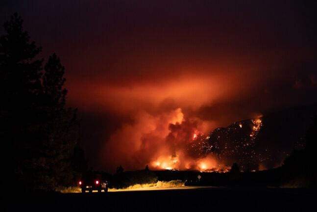 A motorist watches as a wildfire burns on the side of a mountain in Lytton, B.C. on July 1, 2021. (Darryl Dyck / The Canadian Press files)