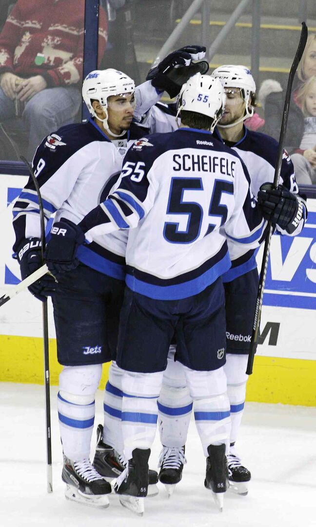 Evander Kane (left) celebrates scoring the game-winning goal Monday with teammates Mark Scheifele, centre, and Michael Frolik.