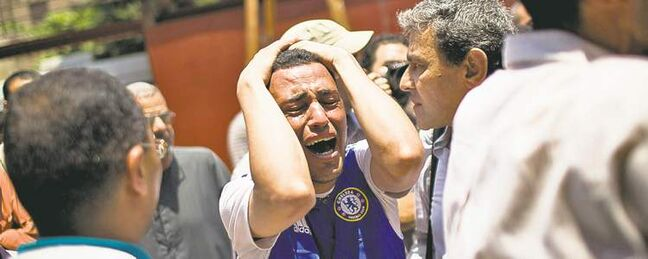An Egyptian man grieves for his brother,  who was killed during a battle in Cairo Monday.