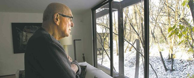 Dr. Jack Fainman in his St. Vital home. He is looking toward the area outside where the gunman fired from.
