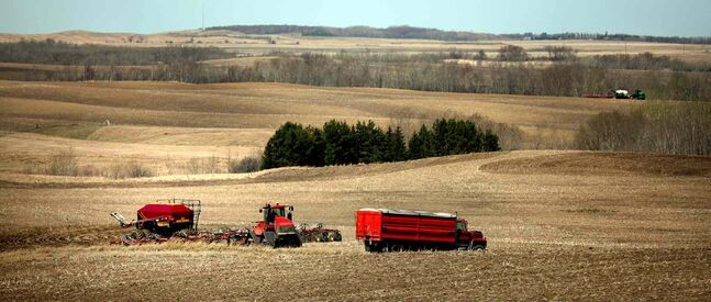 Farm equipment roams the rolling countryside near Cardinal, MB, Friday morning. A dry spring has opened fields to an earlier seeding this year.