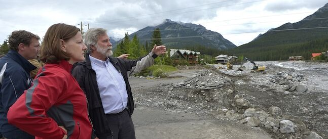 Alberta Premier Alison Redford looks over the devastation at the Cougar Creek area in the town of Canmore, west of Calgary, Monday. At right is Canmore Mayor John Borrowman and at left is Alberta Minister of Municipal Affairs Doug Griffiths.