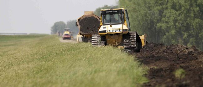 Construction workers bolster the east side of the Portage Diversion on Saturday.
