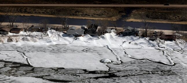 The sun shines on Ochre Beach as piles of ice are seen pressed up against homes.