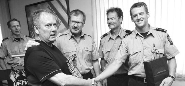 Dennis Gelinas (left) shakes hands with fire paramedic Mark Cortens, who was on the scene along with his captain, Mike Wilcox (second from right), when Gelinas suffered a heart attack in the apartment building where he works. United Fire Fighters of Winnipeg president Alex Forrest (second from left) helped facilitate a reunion so Gelinas could publicly thank Cortens for helping him.