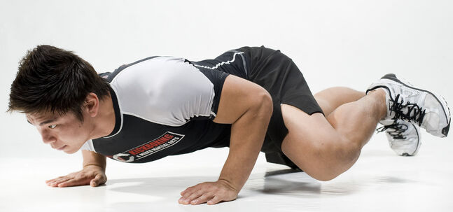 Spiderman pushups are demonstrated by a mixed martial artist trainer from OC Kickboxing and Mixed Martial Arts.