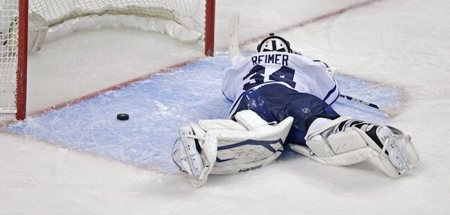 Toronto Maple Leafs goalie James Reimer lays on the ice after letting in Boston Bruins center Patrice Bergeron's overtime series-winning goal.