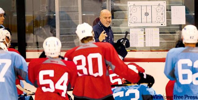 Jets assistant coach Charlie Huddy explains the program to Group B as the team works out on Friday.