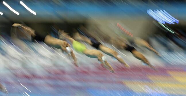 Swimmers start in a men's 100-metre freestyle swimming heat at the Aquatics Centre in the Olympic Park during the 2012 Summer Olympics. (AP Photo/Matt Slocum)