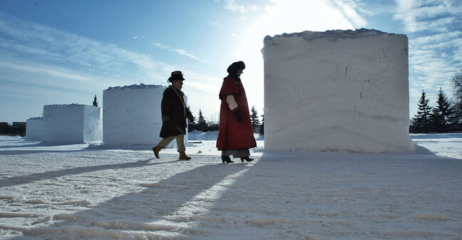 Joanne and her husband Guy Noël, dressed in traditional costume, pass by blocks of snow ready for carving.