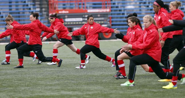 Desiree Scott (centre, with arms extended), with teammates during warm-up as Team Canada practises in preparation for the game against Team USA.