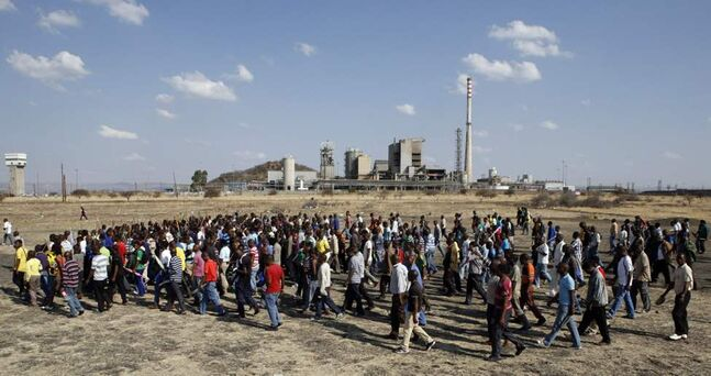 Miners march against Andrew Saffy Memorial Hospital discharging injured colleagues into police custody in Lonmin Platinum Mine near Rustenburg, South Africa. Union rivalry is at the root of violent illegal strikes that have been troubling the mining industry that is the engine driving Africa's largest economy. (AP Photo/Themba Hadebe)