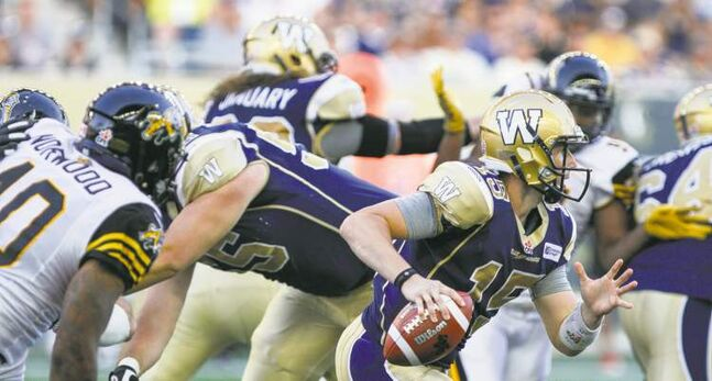 JESSICA BURTNICK / WINNIPEG FREE PRESSBombers QB Max Hall evades TiCats defenders while looking for an open receiver during the Blue and Gold�s 37-18 loss at Investors Group Field Friday night.