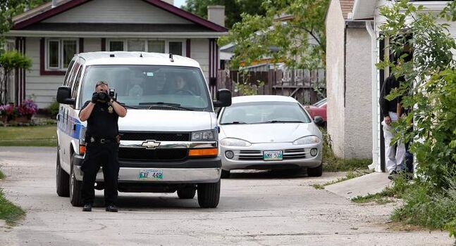 A Winnipeg Police Service identification unit officer takes photos Sunday of the alley behind the home on Bondar Bay where police say a 19-year-old man was found unresponsive after a fight at another home in the neighbourhood late Friday night. The male victim was pronounced dead on Saturday after being transported from the house.