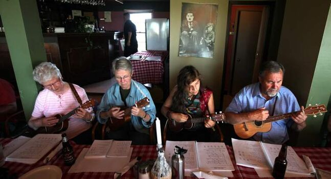 Audrey Brown (from left) Keith Fulton, Genevieve Manahan and Chris Greaves strum along with their songbooks.