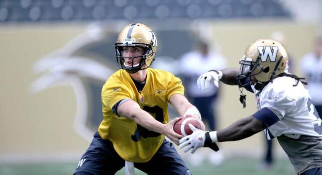 Winnipeg quarterback Justin Goltz (left) hands the ball to tailback Will Ford during Thursday's practice at Investors Group Field.