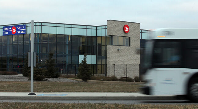 A city Transit bus pulls up in front  of Canada Post's new airport facility.