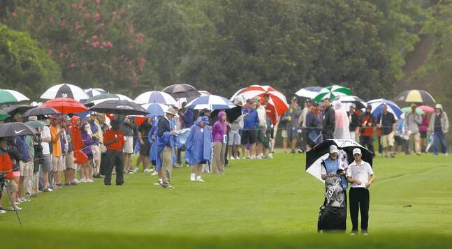 Zach Johnson huddles with his caddy as the rains pelt down during the third round of the Wyndham Championship at Sedgefield Country Club in Greensboro, N.C. on Saturday. Johnson shot 65.