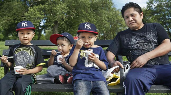 Pedro Monguia, 28, sits on a bench in a neighborhood park with his three sons, Jonathan, 7, Landon, 3, and Giovanni, 5, after treating them to ice cream, in the Brooklyn borough of New York.